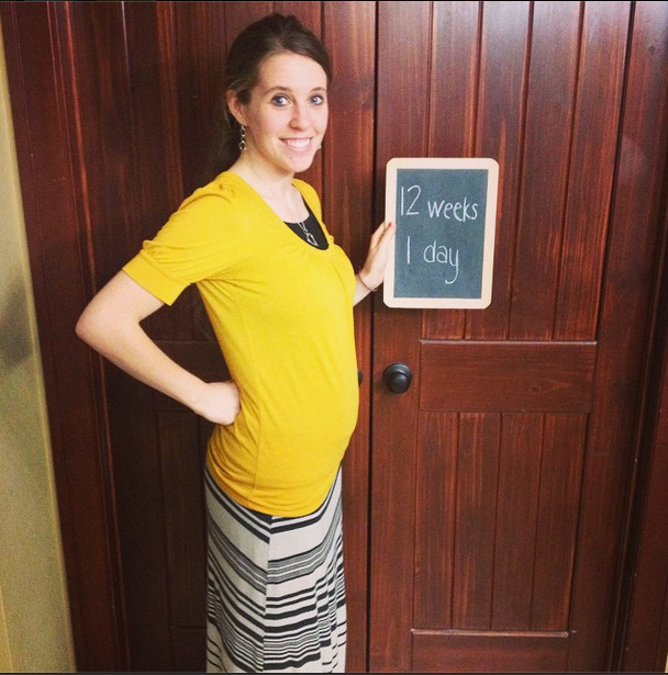 In the pic, Jill poses with her hand on her hip, with her stomach slightly  protruding, while holding a chalkboard that reads, '12 weeks, 1 day.